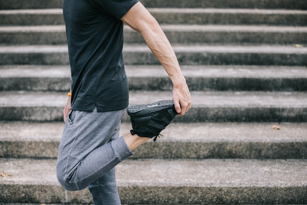 De mens werkt het uitrekken van benen uit voor het opwarmen vóór het uitoefenen van en het beklimmen van treden.