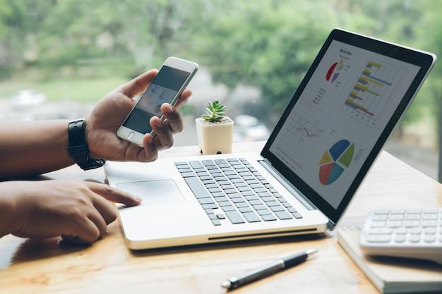De mens werkt met een slimme telefoon en een laptop in zijn bureau