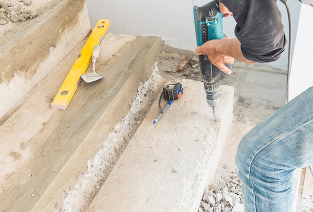 De mens werkt met het versterken van de betonnen wijziging van de trapstructuur met behulp van een handboor