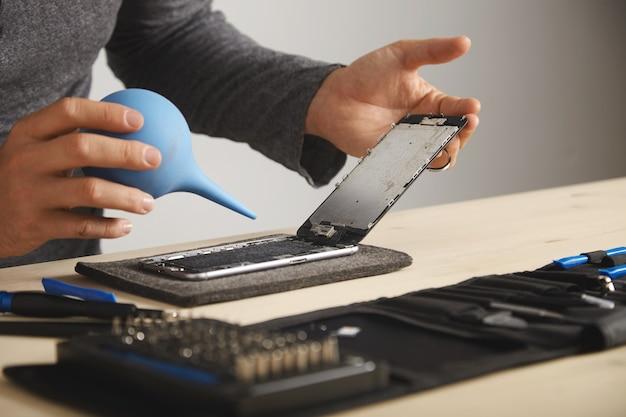 De mens werkt zorgvuldig in zijn laboratorium om slimme telefoon te repareren en schoon te maken met behulp van een spuit om al het stof uit het apparaat te blazen