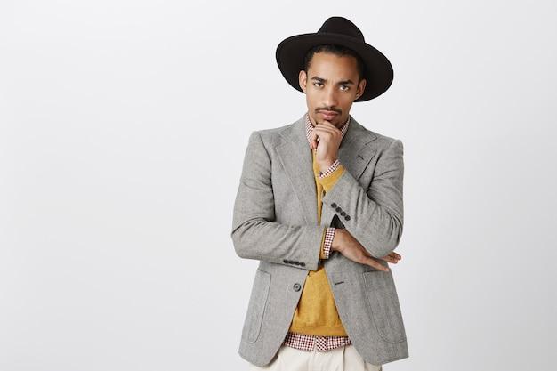 De mens wordt serieus als het om werk gaat. portret van knappe gerichte jonge donkere man in stijlvolle hoed en outfit, hand op kin, starend, moeilijke beslissing nemen over grijze muur