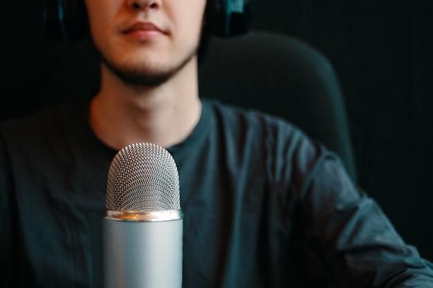 De mens zendt op de lucht uit op een spreker. podcaststudio met microfoon, koptelefoon en stoel. een deel van het gezicht
