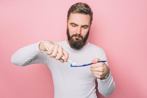 De mens zet wat tandpasta op een tandenborstel