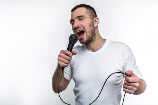 De mens zingt lied in microfoon en rockt uit