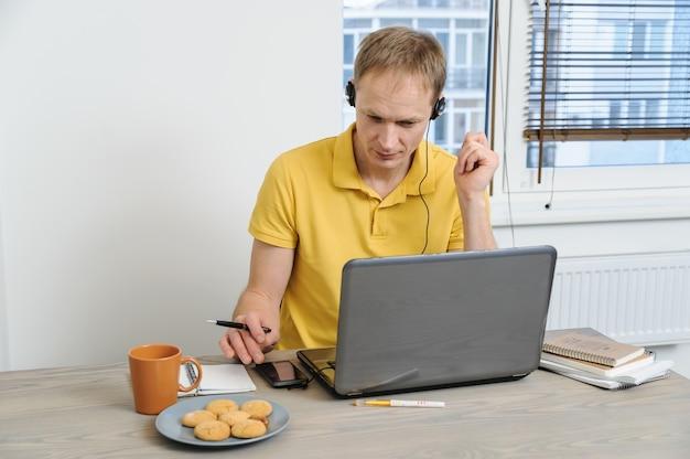 De mens zit aan een tafel en kijkt naar het laptopscherm