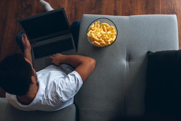 De mens zit alleen op vloer met gekruiste benen en houdt laptop op het. film kijken, sportprogramma. zichzelf vermaken. bekijk.