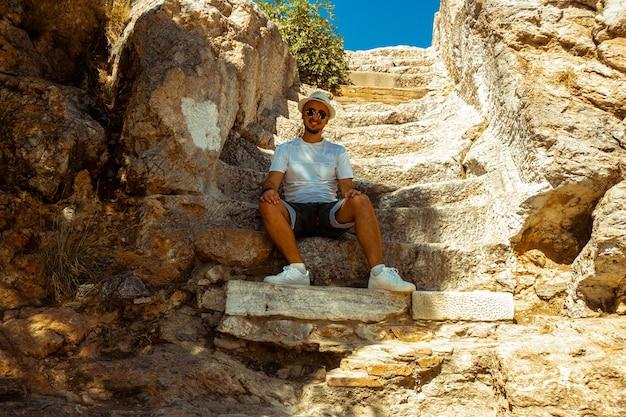 De mens zit bij de oude griekse ruïnes