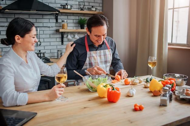 De mens zit bij lijst in keuken en sneed groenten voor salade.
