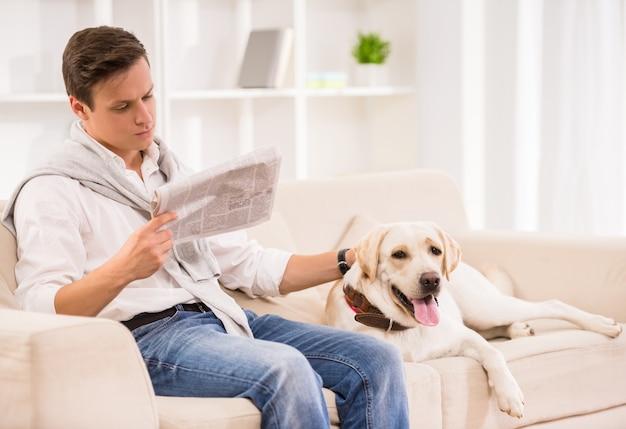 De mens zit op bank met hond en leest een krant.