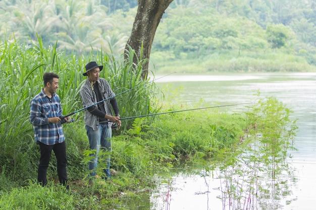 De mens zit op de rivieroever vissende vissen