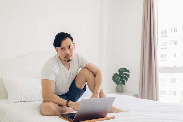 De mens zit op het bed en werkt op zijn laptop.