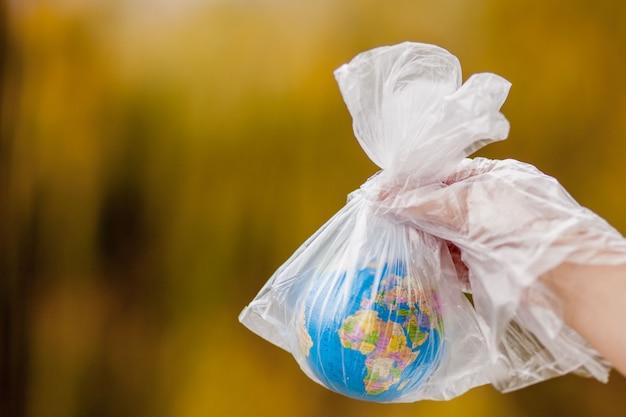 De menselijke hand houdt de planeet aarde in een plastic zak. het concept van vervuiling door plastic puin. opwarming van de aarde door broeikaseffect.