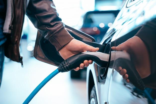 De menselijke hand houdt het elektrische auto laden verbindt met elektrische auto