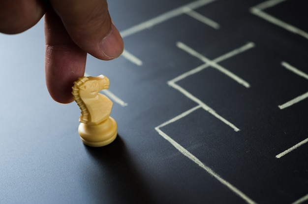 De menselijke hand plaatst ridderschaak bij labyrint binnengaat