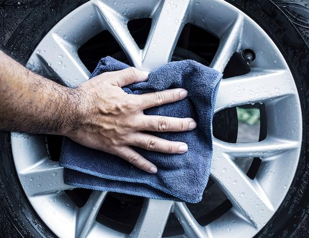 De menselijke hand veegt het lichtmetalen wiel van de auto af met een microvezeldoek