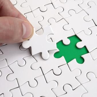 De menselijke hand vult de laatste ontbrekende elementen van het oppervlak uit de legpuzzel.
