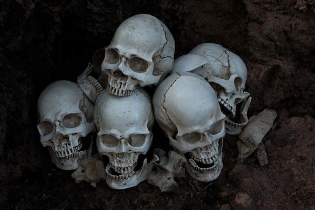 De menselijke schedel en de stapel botten op zwarte achtergrond, halloween-nacht