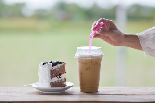 De mensen drinken ijskoffie in koffie met kokosnotencake, ijskoffie op houten lijst