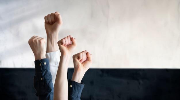 De mensen met opgeheven handen vuisten in de lucht als symbool van protest voor gelijkheidsvrijheid