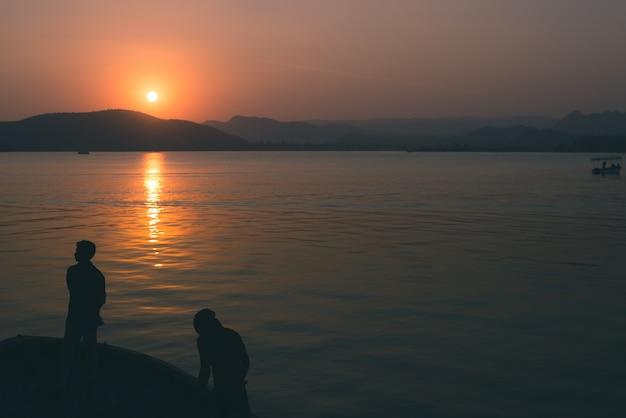 De mensen silhouetteren bij zonsondergang in backlight, de voorzijde van het riviermeer, overweldigend landschap. afgezwakt beeld.