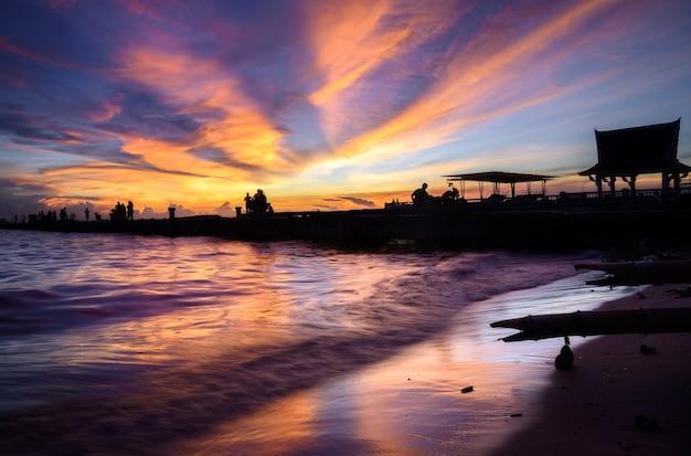 De mensen silhouetteren op de zee met avondrood