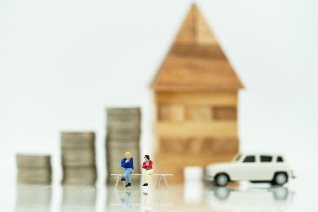 De mensen van mainature die zich met muntstukkenstapel en huis bevinden. home financiële investeringen concept.