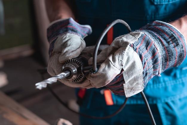 De mensenbouwer in overall en handschoenen plaatst een grote boor op een boom in een boorclose-up.