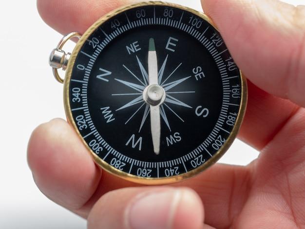 De mensenhand die van de close-up gouden kompas op witte achtergrond houdt