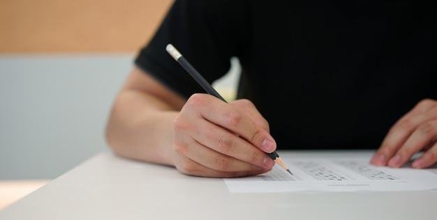 De mensenhand die van de student potlood voor het doen van tekstexamen gebruikt