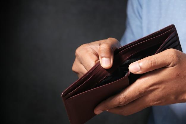 De mensenhand opent een lege portefeuille met exemplaarruimte.