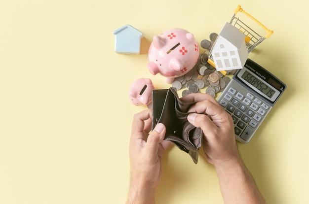 De mensenhand opent een lege portefeuille met spaarvarken