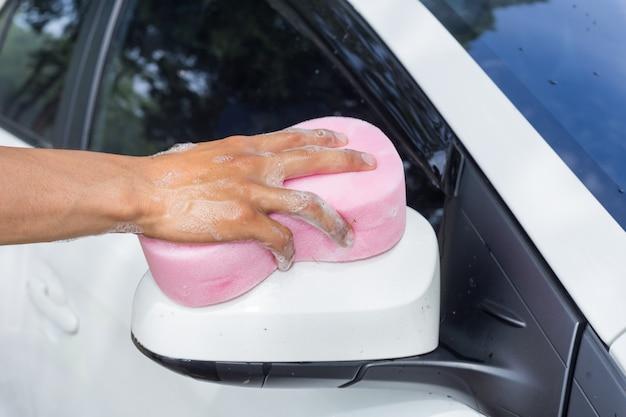 De mensenhanden houden spons voor het wassen van witte auto