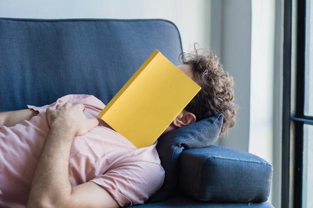 De mensenslaap op bank met boek behandelt zijn gezicht