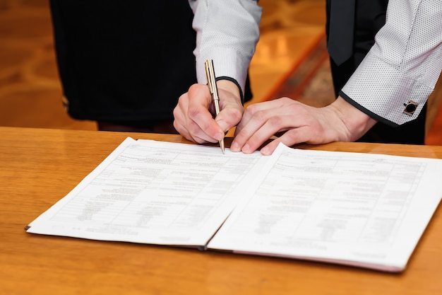 De mensenzakenman ondertekent documenten met een pen