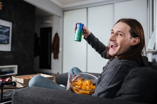 De mensenzitting die thuis binnen binnen chips eten let op tv