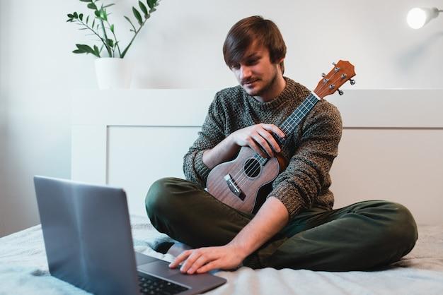 De mensenzitting thuis leert ukelele spelen met behulp van online lessen.