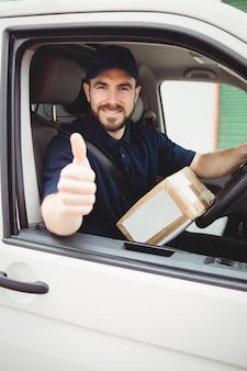 De mensenzitting van de levering in zijn bestelwagen met omhoog duimen