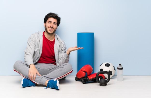 De mensenzitting van de sport op de vloer die copyspace denkbeeldig op de palm houdt om een advertentie in te voegen