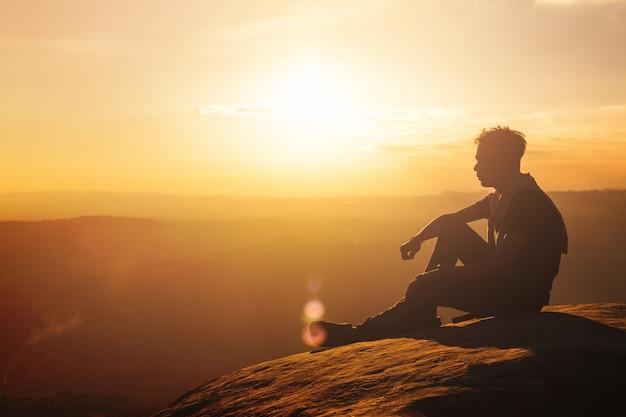 De mensenzitting van het silhouet bovenop mouatain tijdens mooie zonsondergangachtergrond