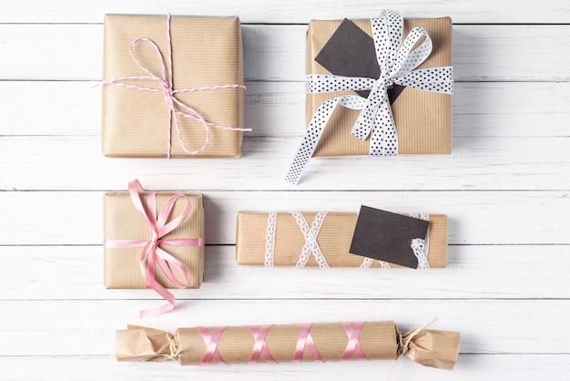 De met de hand gemaakte gift in dozen gedaan op een witte houten vlakke achtergrond, legt