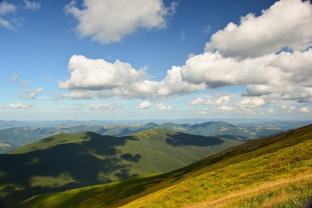 De met groen gras begroeide bergkam wordt fel verlicht door de zon, van bovenaf geschoten. daarboven is een bewolkte blauwe lucht.