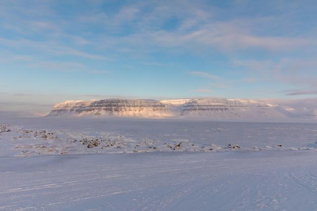 De met ijs bedekte fjord tempelfjorden, met de berg templet en de sneeuwscooterbaan op de voorgrond. svalbard, noorwegen.