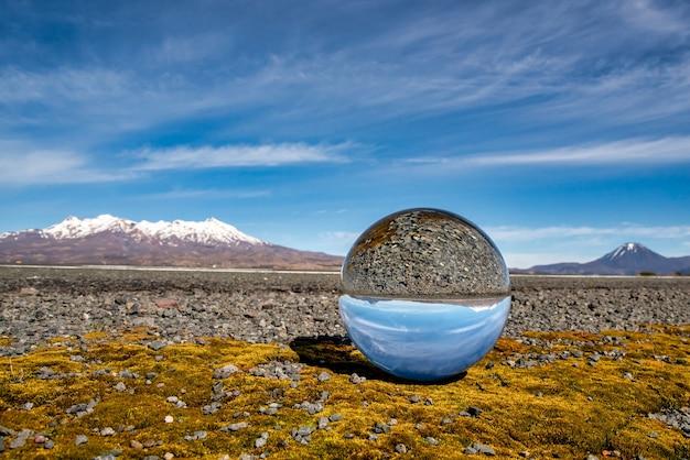 De met sneeuw bedekte vulkanen van het central plateau in de desert road weerspiegeld in een kristallen bol zittend op wat geel mos aan de kant van state highway one