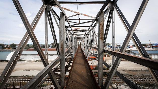 De metalen brug van hun structuren tegen de achtergrond van een bouwplaats