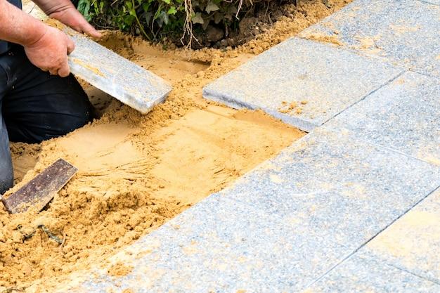 De metselaar legt grindplaten op zand om een steegje te maken