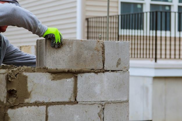 De metselarbeider maakt concrete muur door cementblok en pleister bij bouwwerf