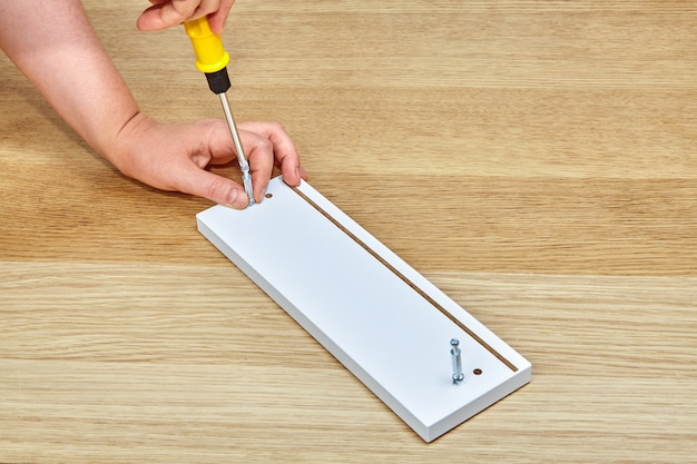 De meubelmaker draait de verbindingsbouten met een schroevendraaier in een houten meubel, met één hand houdt hij meubels vast