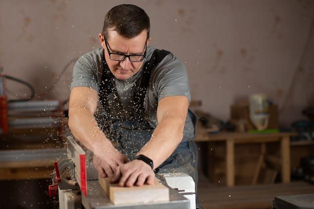 De meubelmaker zaagt hout en zaagsel