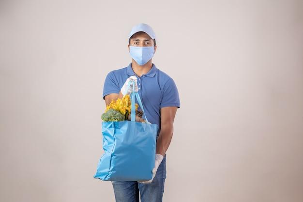 De mexicaanse leveringsman laadde ecologische zak met groenten en fruit die gezichtsmasker en handschoenen dragen
