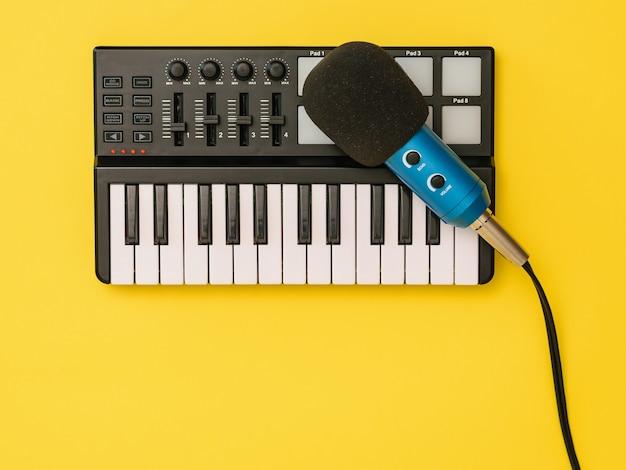 De microfoon voor muziekmixer op een gele achtergrond. het concept van werkplekorganisatie. apparatuur voor het opnemen, communiceren en luisteren naar muziek.